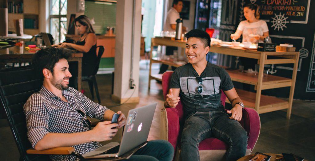 Two men on laptops smiling